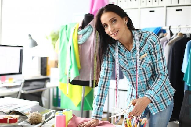 Tijeras de mujer costurera corta tela en taller de costura y reparación. concepto de desarrollo de pequeñas y medianas empresas.