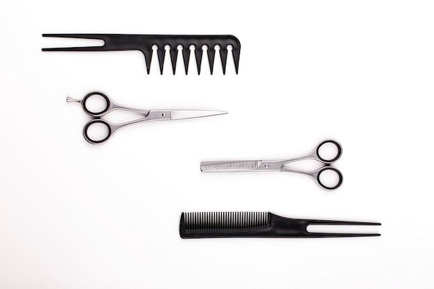 Las tijeras y los peines para el corte y el tratamiento del pelo mienten en una tabla blanca
