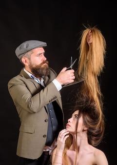 Tijeras de peluquero. mujer corte de pelo por peluquero. peluquero visita mujer en peluquería. chica modelo de belleza con cabello sano