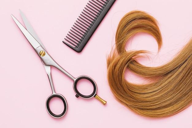 Tijeras de peluquero, peine y un mechón de cabello rizado rubio bebé sobre un fondo rosa