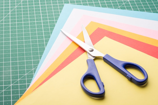 Tijeras sobre un montón de papeles de diferentes colores