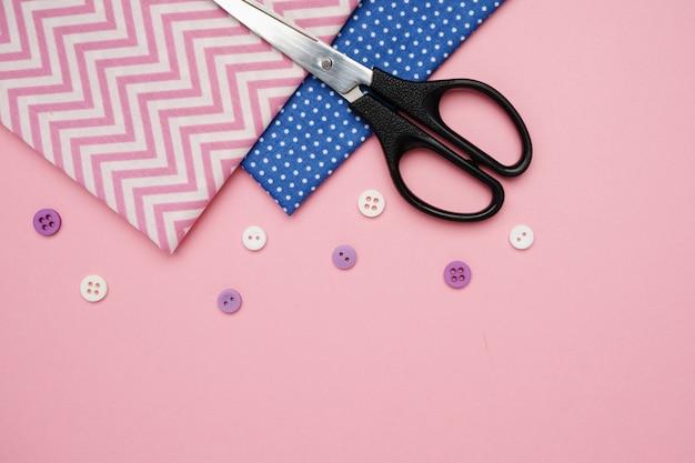 Tijeras, telas y botones para coser con espacio de copia