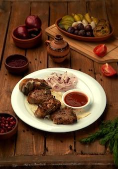 Tikka kebab servido con aros de cebolla fresca y salsa de tomate