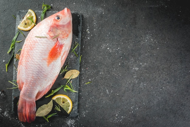 Tilapia roja de pescado crudo en una tabla de cortar sobre una mesa de piedra negra, con especias, limón y hierbas para cocinar. vista superior copyspace