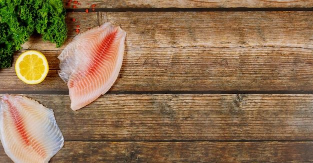 Tilapia rosa con limón y col rizada sobre fondo de madera.