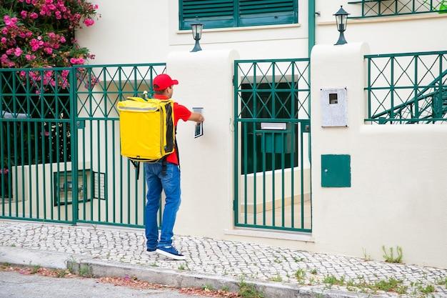 Timbre de llamada de mensajero de alimentos, sosteniendo la tableta, entregando alimentos a la puerta. concepto de servicio de envío o entrega