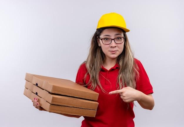 Tímida joven repartidora en polo rojo y gorra amarilla sosteniendo la pila de cajas de pizza apuntando con el dedo a ella sonriendo