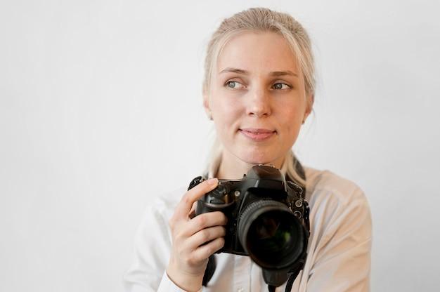 Tímida linda chica sosteniendo una cámara profesional