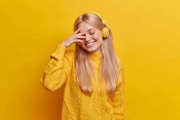 Tímida mujer rubia positiva sonríe ampliamente cierra los ojos disfruta escuchando su música favorita a través de auriculares inalámbricos pasa tiempo libre sola con canciones agradables usa suéter