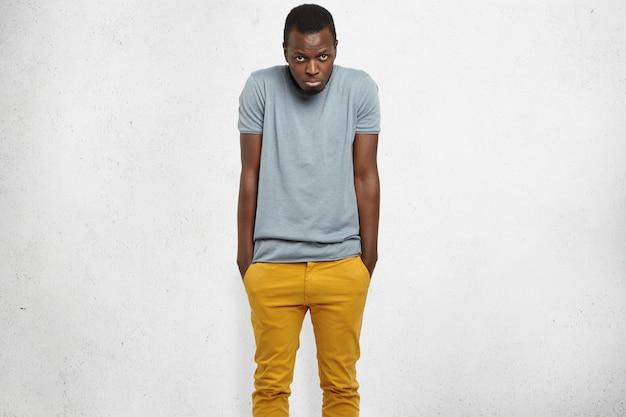 Tímido apuesto joven afroamericano que se siente avergonzado o incómodo, encogiéndose de hombros, manteniendo las manos en los bolsillos de sus jeans mostaza, mirando con expresión infeliz, haciendo pucheros