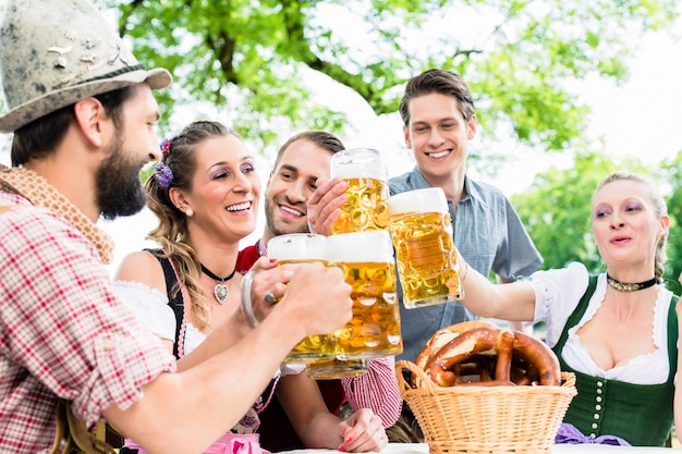 Tintinear vasos con cerveza en pub bávaro
