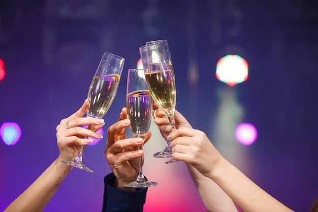 Tintineo de copas de champán en manos sobre fondo de luces brillantes