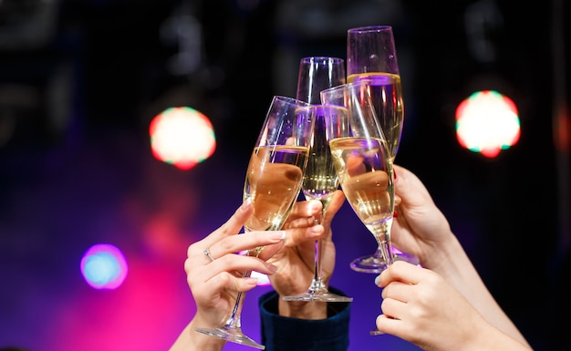 Tintineo de copas de champán en las manos sobre fondo de luces brillantes
