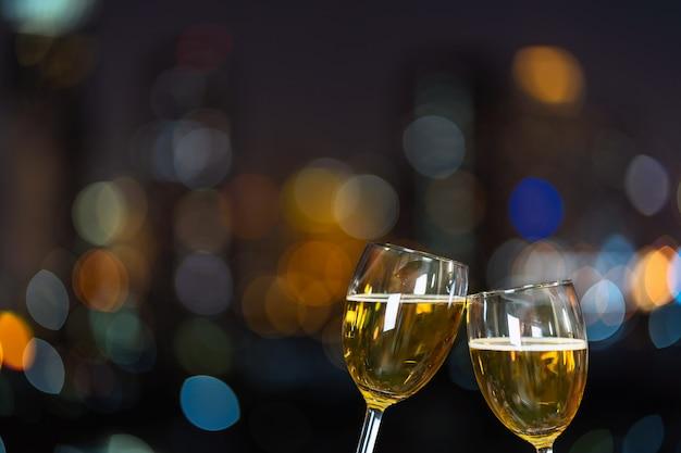 Tintineo con dos jarras de cerveza o vasos sobre la foto borrosa del paisaje urbano para celebrar
