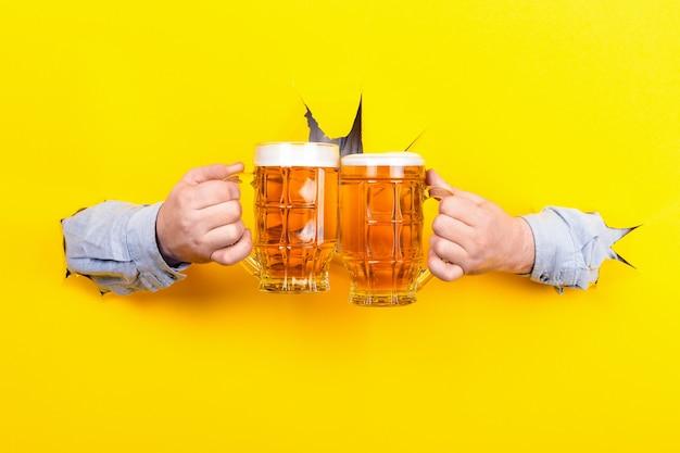 Tintineo de vasos con cerveza sobre fondo amarillo