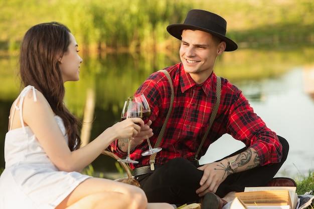 Tintineo de vasos. pareja joven caucásica, feliz disfrutando de fin de semana juntos en el parque el día de verano.