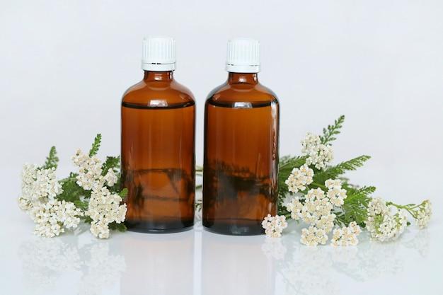Tintura de milenrama, aceite de milenrama. aceite de milenrama en dos botellas de vidrio marrón y flores de milenrama farmacia natural