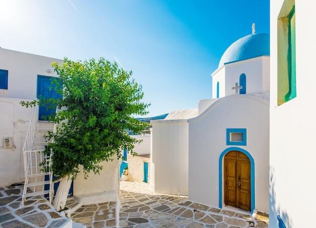 Típica iglesia encalada con cúpula de color azul en la esquina de la calle, lefkes, isla de paros, grecia