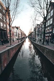 Típico canal holandés en amsterdam con edificios y autos tradicionales holandeses