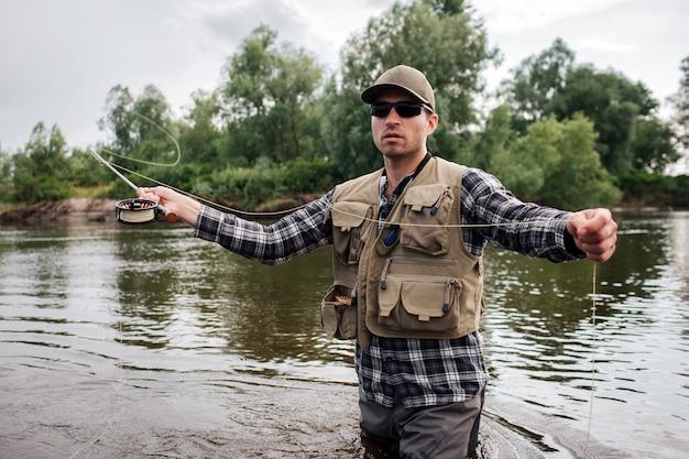 Tipo brutal y tranquilo de pie en el agua y mirando hacia adelante. él tiene caña de mosca en una mano y una cuchara en la otra. guy va a pescar.