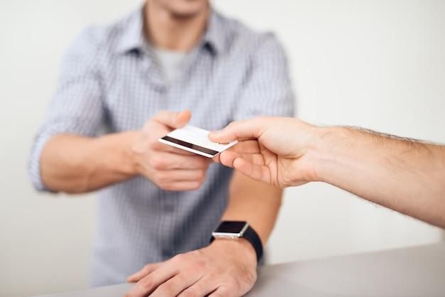El tipo le está dando una tarjeta de crédito al vendedor.