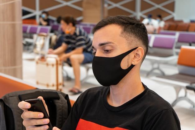 Un tipo está esperando un vuelo con una máscara médica en la cara en la sala del aeropuerto. viajes aéreos durante la pandemia de coronavirus.