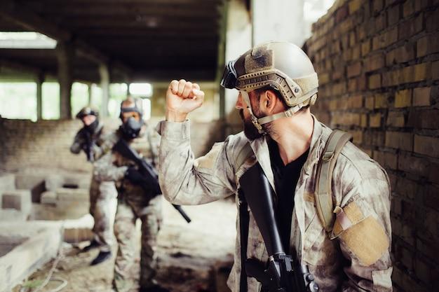 Un tipo fuerte está de pie en una gran sala abierta con sus camaradas y los mira. él está shwoing puño. otros tipos lo miran y sostienen rifles negros.