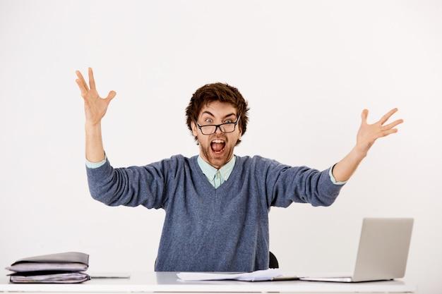 El tipo pierde los estribos en el trabajo, se sienta en el escritorio de la oficina con una computadora portátil y apila documentos, levanta las manos consternado, grita molesto y angustiado