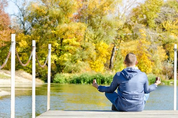 El tipo en la postura del loto se sienta en el muelle. otoño soleado. vista trasera