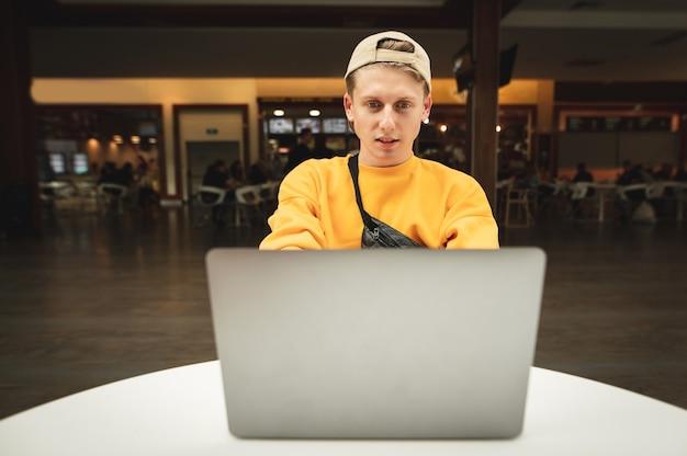 Un tipo con ropa de calle elegante y una gorra se sienta en un café y trabaja en una computadora portátil.