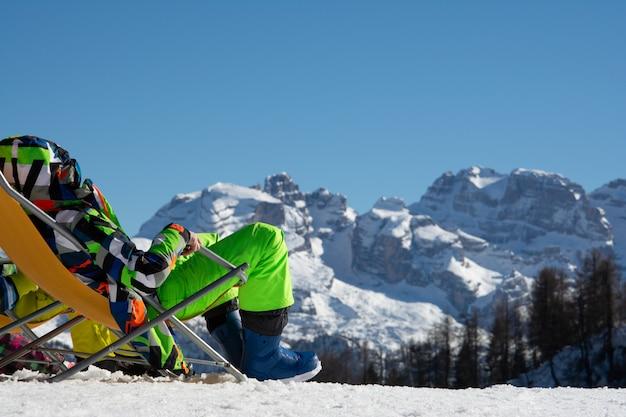 El tipo el snowboarder se sienta en una tumbona y mira las montañas.