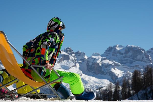 El tipo el snowboarder se sienta en una tumbona en una pista de esquí.