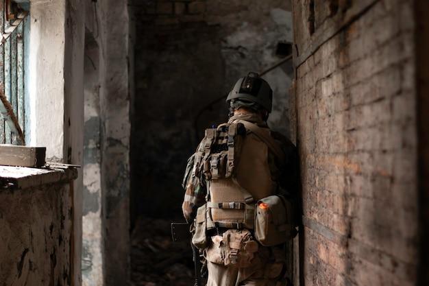 Un tipo con un uniforme militar estadounidense en un antiguo pasillo abandonado se mueve con una pistola airsoft sports gam
