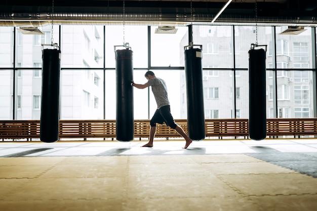 Un tipo vestido con la camiseta gris y pantalones cortos negros está en guardia y trabaja con un puñetazo de boxeo junto a un saco de boxeo colgando contra el fondo de las ventanas panorámicas del gimnasio.