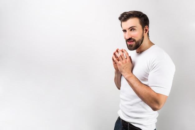 Un tipo con una visión astuta está juntando sus dedos en ambas manos. ha inventado algo y quiere hacerlo lo antes posible. aislado en la pared blanca