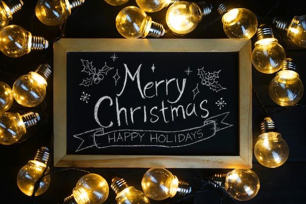 Tipografía de feliz navidad en pizarra entre bombillas en madera negra