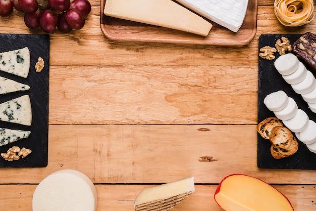 Tipos de queso; uvas; nogal y pasta dispuestas en marco sobre superficie de madera.