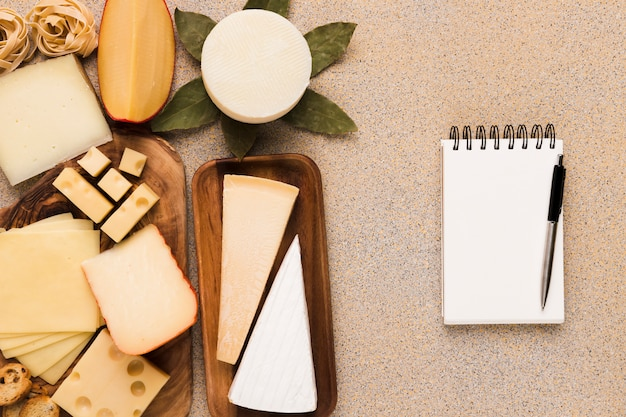 Tipos sanos de quesos en la placa de madera con la libreta y la pluma blancas en blanco