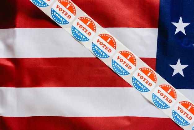 Tira de adhesivos voto hoy en la bandera de los estados unidos después de votar en la urna.