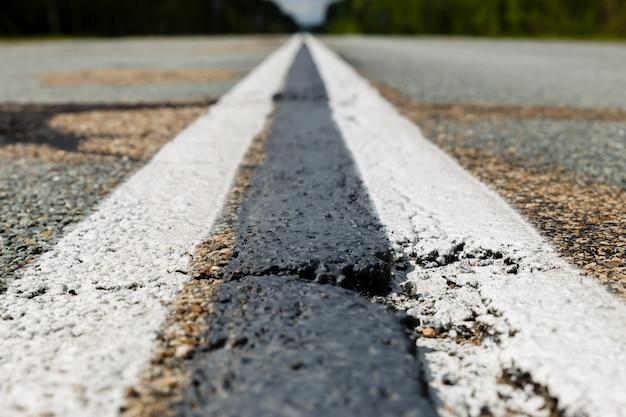 Tira continua blanca doble en la carretera de asfalto.