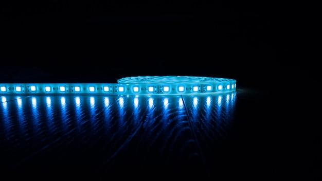 Tira de luz led azul brillante sobre fondo oscuro con espacio de copia
