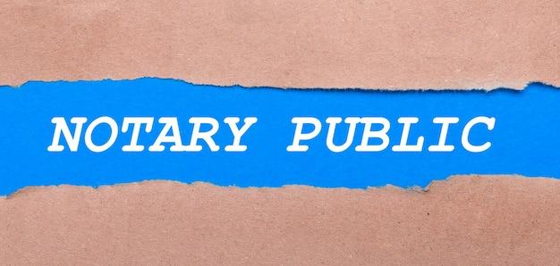 Una tira de papel azul con la inscripción notario público entre el papel marrón. vista desde arriba