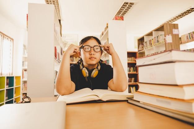 Tirado del estudiante asiático joven que se sienta en la tabla. estudiante joven que estudia en biblioteca.