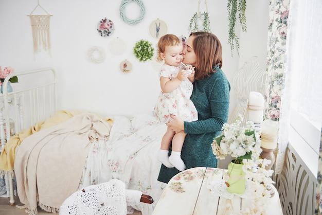 Tirado de la madre feliz que juega con su bebé en sala de niños del vintage. el concepto de infancia feliz y amor maternal.