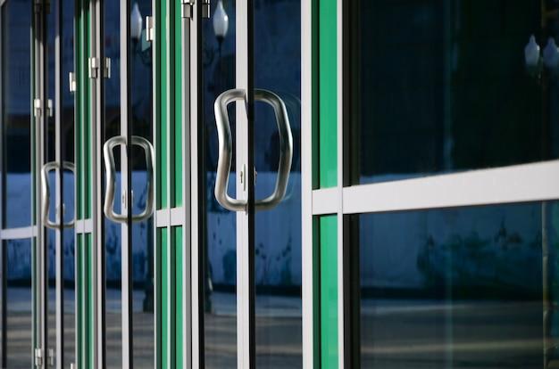 Tirador de puerta cromado y vidrio de moderna fachada de oficina de aluminio