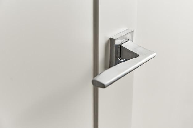 Tirador de puerta plateado sobre puerta blanca. accesorios de mobiliario, elemento interior