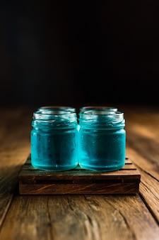 Tiradores alcohólicos de color azul, o tragos en la mesa de madera, con espacio de copia