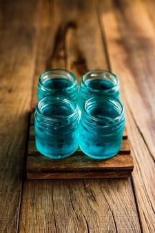 Tiradores alcohólicos de color azul, o tragos en la mesa de madera