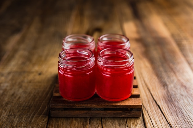 Tiradores alcohólicos de color rojo, o tragos en la mesa de madera