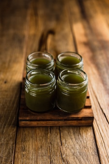 Tiradores alcohólicos de color verde, o tragos en la mesa de madera